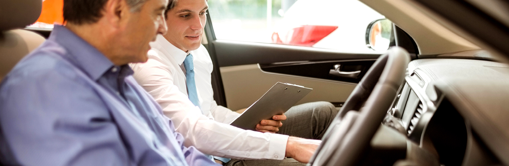 Man in car talking with car salesman about a new car purchase