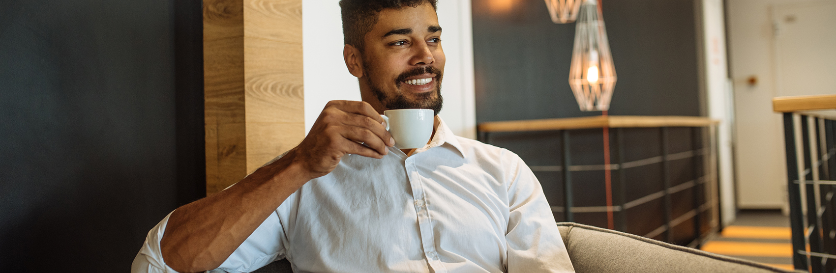 Young man drinking a cup of coffee at home