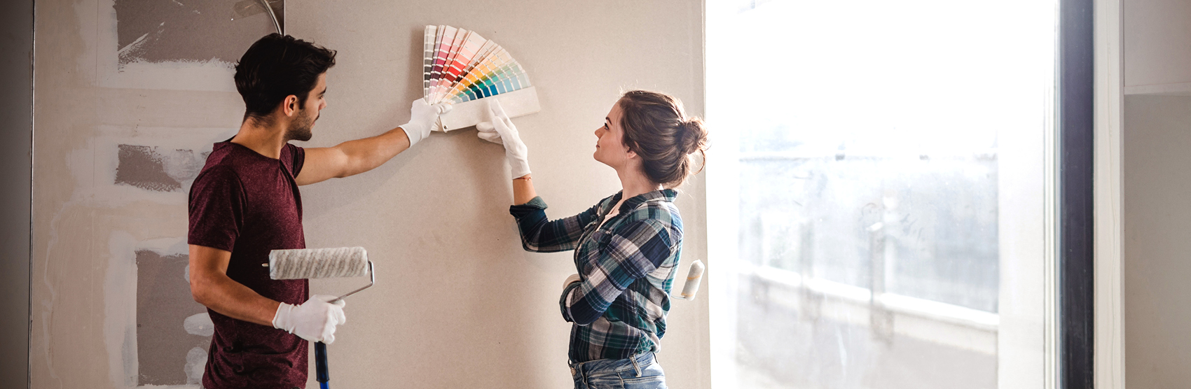 Young couple reviewing paint swatches before painting a wall in their house