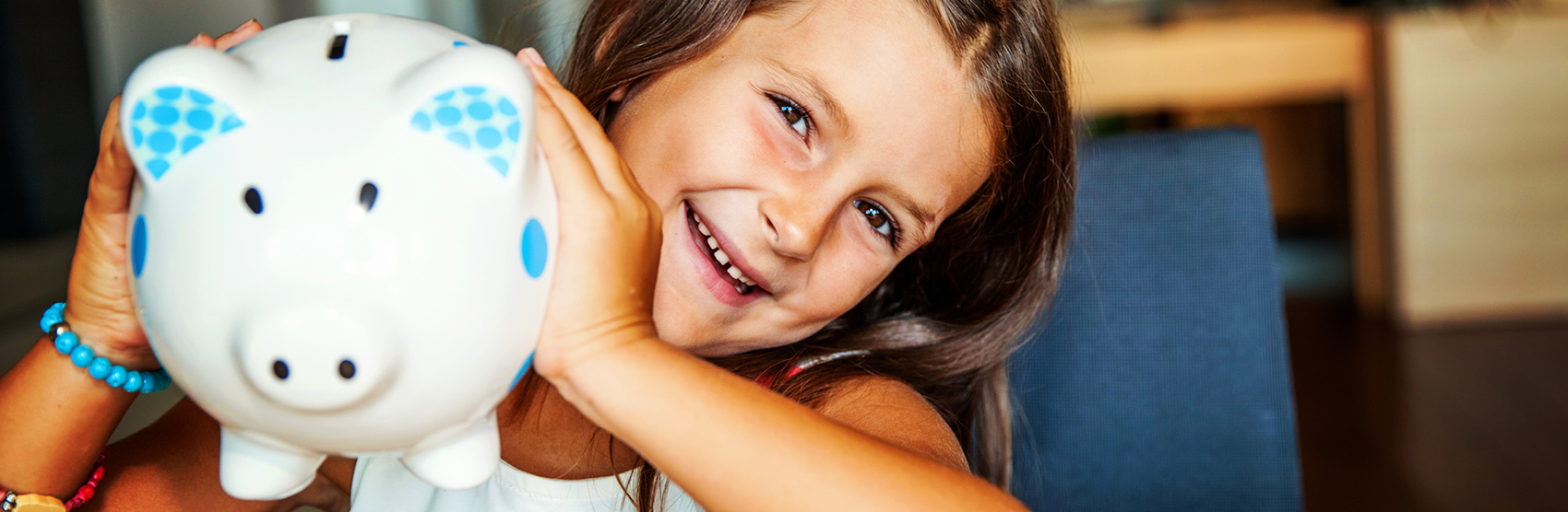 Smiling girl holding white piggy bank