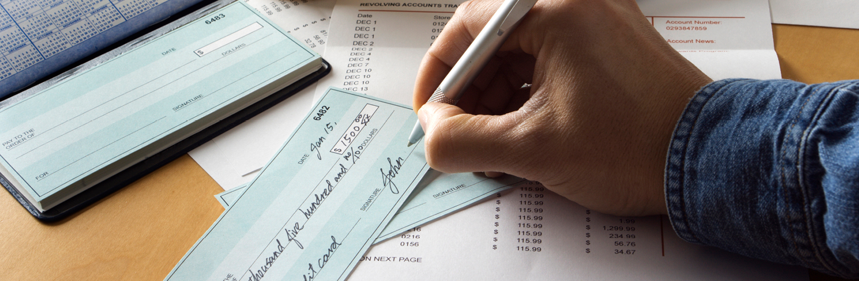 Picture of bills and person writing a check