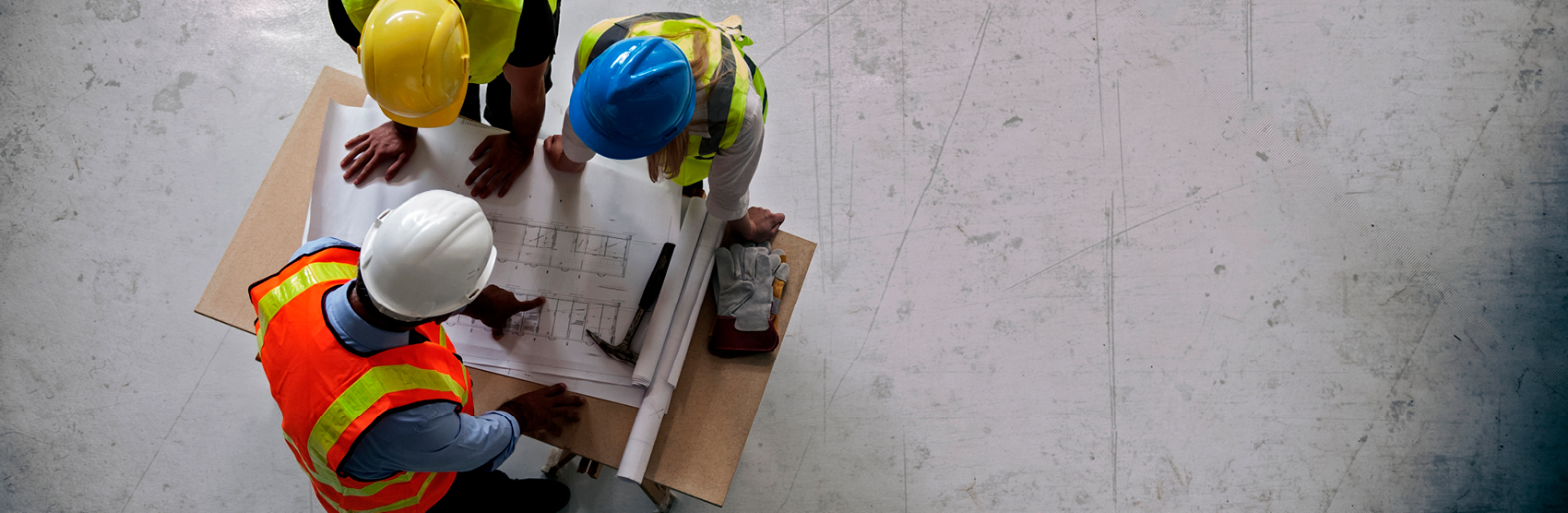 Three architects wearing hard hats looking at renderings