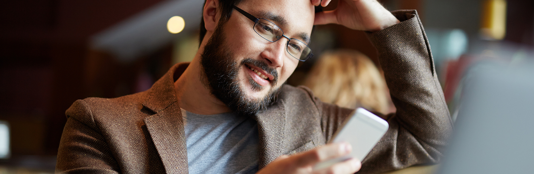 Man with beard looking at mobile device